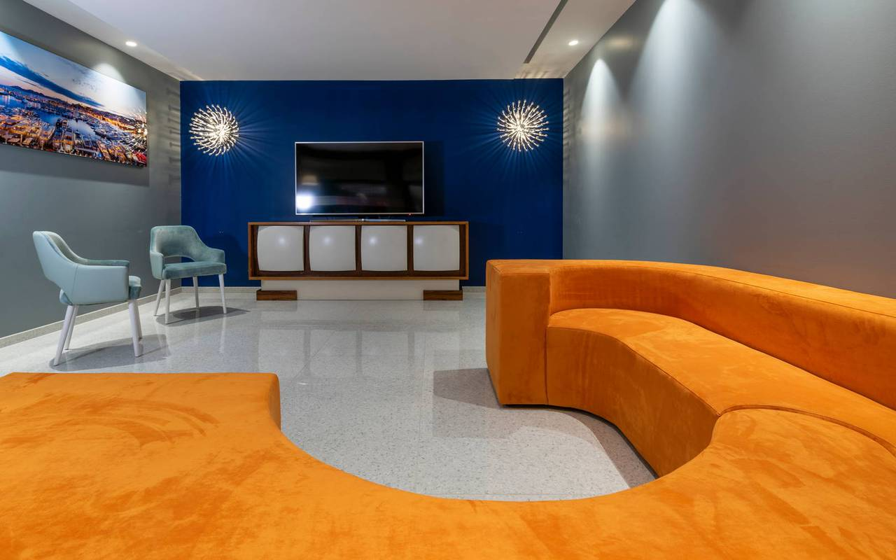 Living room with orange sofa and large television, 4 star hotel french riviera, Juliana Hotel Cannes.